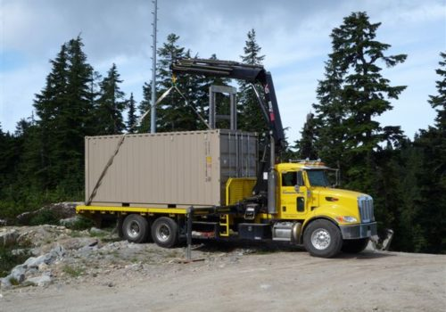 Crane truck unloading 20' container at site.